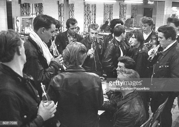 Rockers British youths into leather scruffy clothes motorcyles rock music enjoying sodas at a roadside cafe