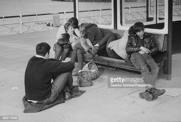 Rockers resting on a bench w their girlfriends Rockers are British youths into leather motorcycles rock music etc