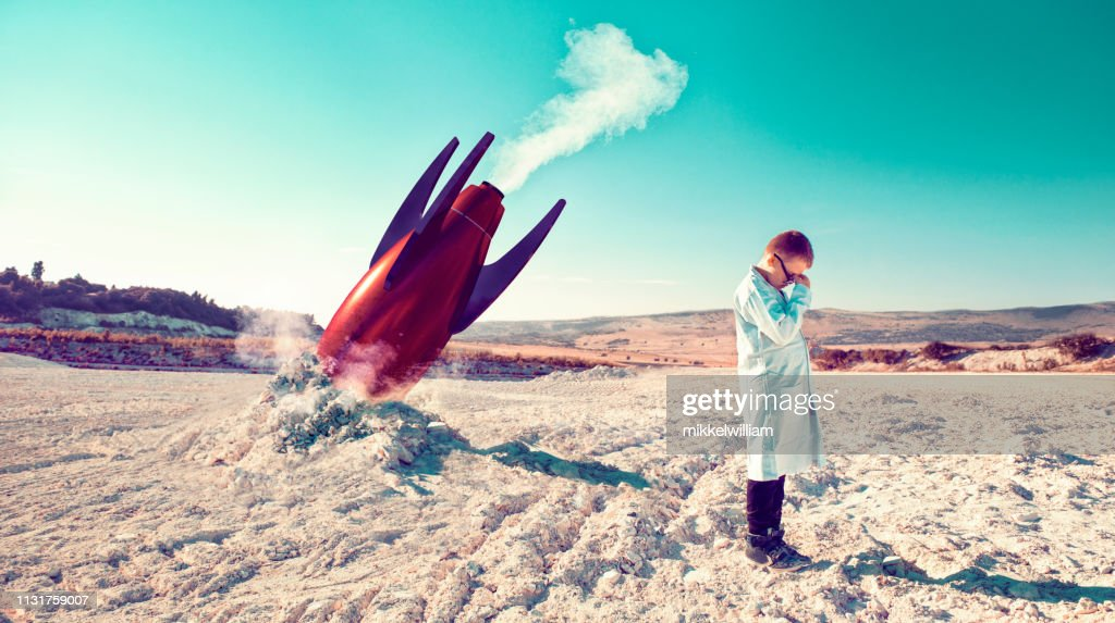 Rocket fails and falls to the ground while child in lab coat shows his disbelief : Stock Photo