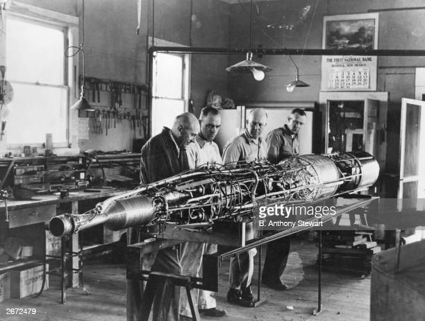 Rocket pioneer Dr Robert Hutchings Goddard on the left and three colleagues working on a rocket with the casing removed