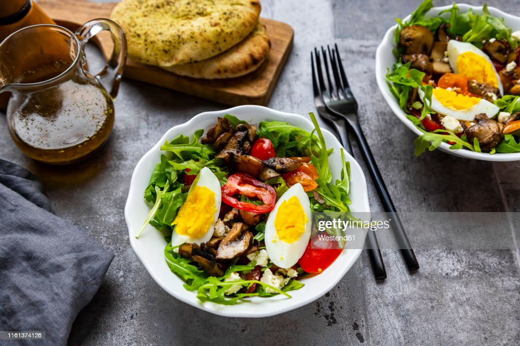 Rocket salad with fried champignons, hard-boiled egg, tomatoes and feta : Stock Photo