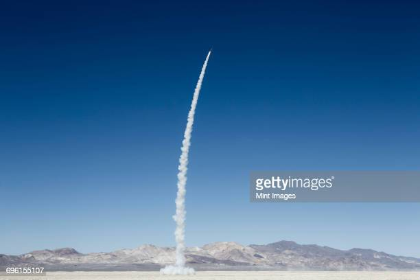 Rocket shooting into vast, desert sky, Black Rock Desert, Nevada