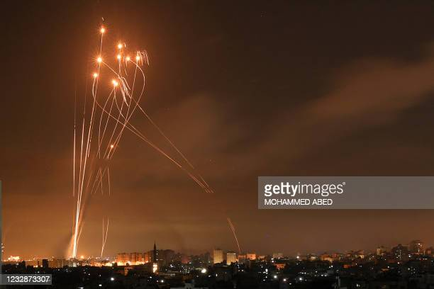 Rockets light up the night sky as they are fired towards Israel from Beit Lahia in the northern Gaza Strip on May 14, 2021. - Israel bombarded Gaza...
