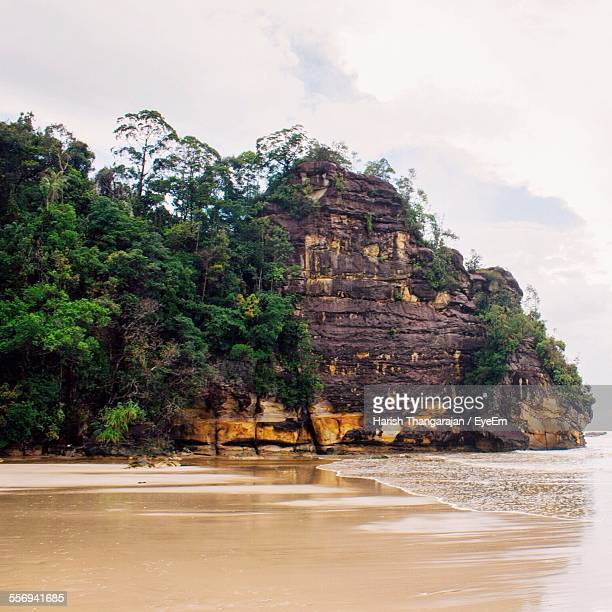 rockface on beach against cloudy sky - bako national park stock pictures, royalty-free photos & images