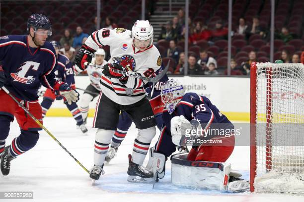 Rockford IceHogs left wing Tyler Sikura attempts to play the airborne puck in front of Cleveland Monsters goalie Matiss Kivlenieks during the first...