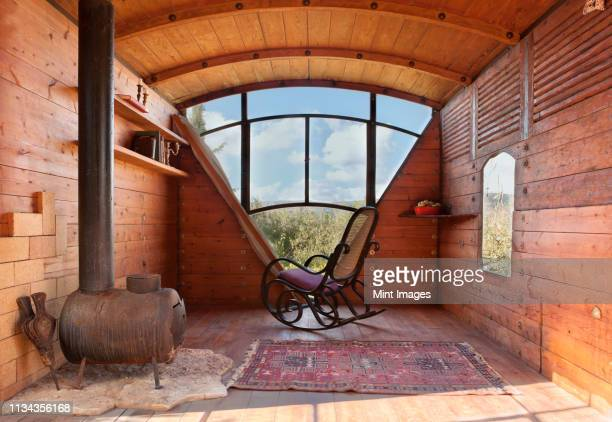rocking chair in wooden seating area - 掘建て小屋 ストックフォトと画像