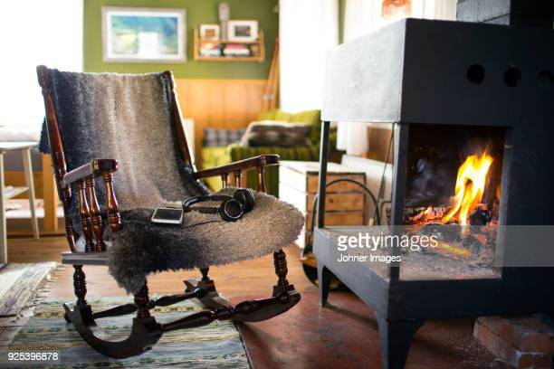 rocking chair next to fireplace - rocking chair stock pictures, royalty-free photos & images