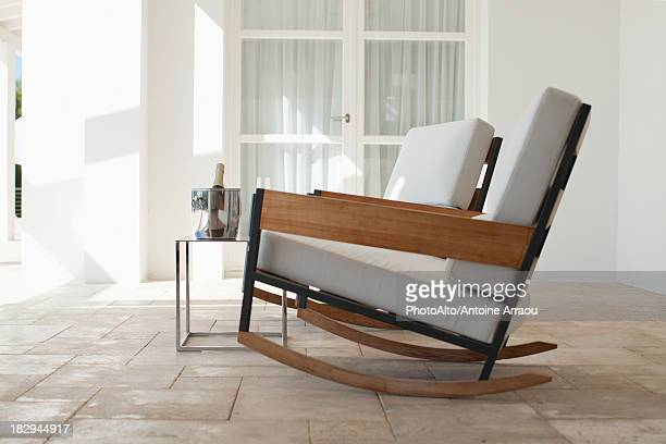 rocking chairs and champagne bucket on patio - rocking chair stock photos and pictures