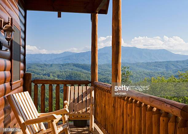 Rocking chairs on the patio outside a mountain cabin