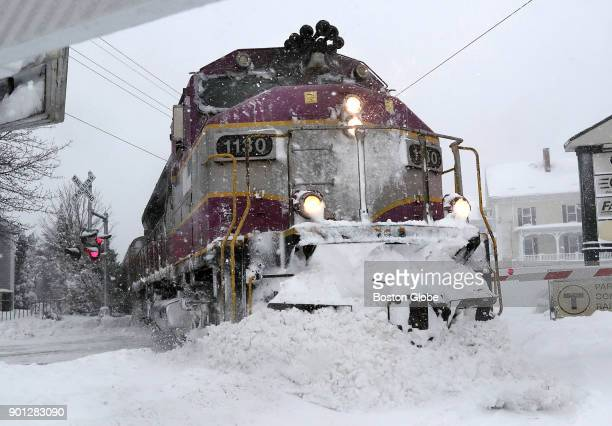 Rockportbound MBTA commuter rail train pushed aside snow crossing Washington St in Gloucester Mass during snow storm on Jan 4 2018