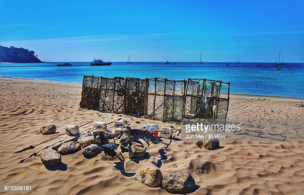 rocks against crab pots on sandy beach - crab pot stock photos and pictures