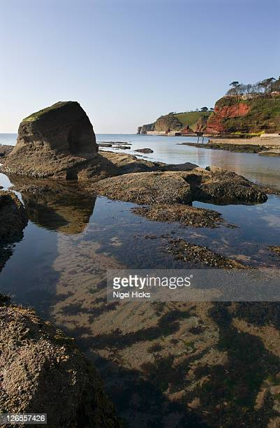 rocks and a tidal pool on the beach, seen at low tide, dawlish, devon, great britain. - low tide stock pictures, royalty-free photos & images