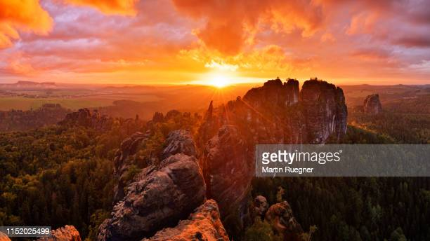 rocks and rock needles of the schrammsteine and falkenstein, at a dramatic sunset. - wilderness area stock pictures, royalty-free photos & images