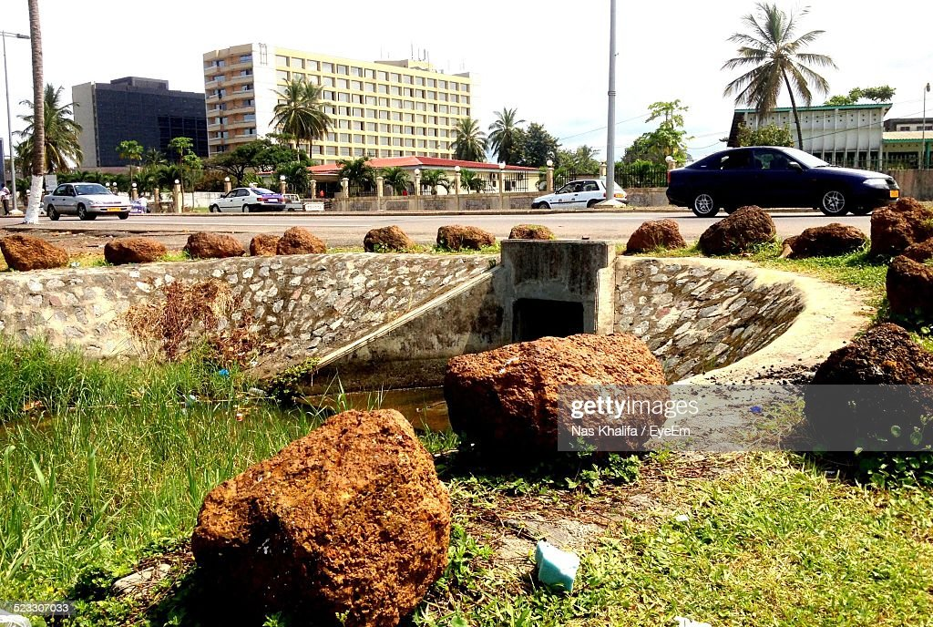 Rocks Arranged At Canal By Street In City : Stock Photo