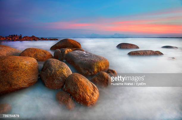 Rocks At Sea Shore Against Sky During Sunset
