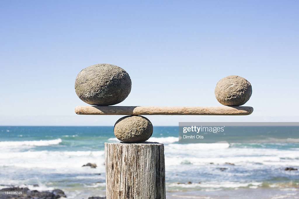 Rocks balancing as scale on wooden plank : Stock Photo