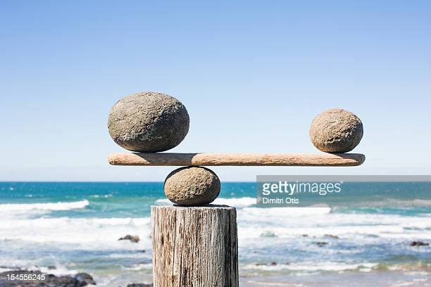 Rocks balancing as scale on wooden plank