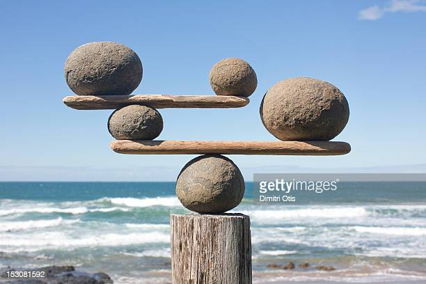 rocks balancing on driftwood, sea in background - pietra roccia foto e immagini stock