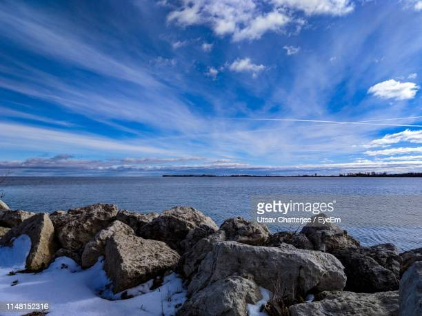 rocks by sea against blue sky - manitoba stock pictures, royalty-free photos & images