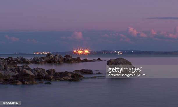 rocks by sea against sky at sunset - krasimir georgiev stock photos and pictures