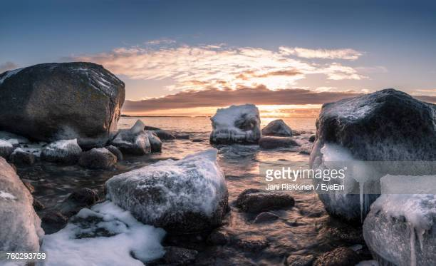 Rocks By Sea Against Sky During Sunset