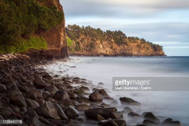 rocks by sea against sky - punalu'u_beach stock pictures, royalty-free photos & images