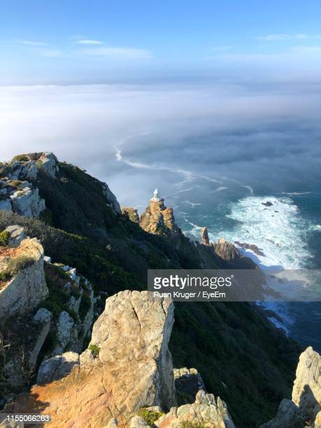 rocks by sea against sky - rocky coastline stock pictures, royalty-free photos & images