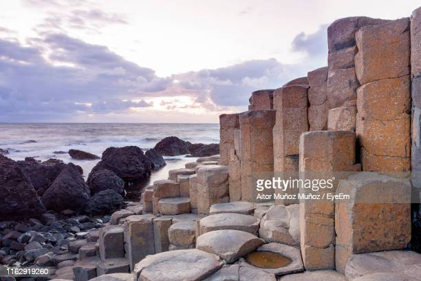 rocks by sea against sky - giant's causeway stock pictures, royalty-free photos & images
