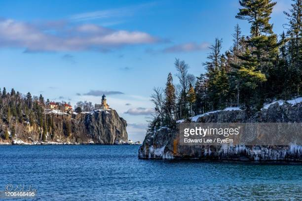 rocks by sea against sky - lake superior stock pictures, royalty-free photos & images