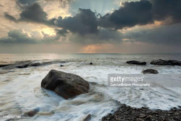 rocks by the stormy sea at sunset - seascape stock-fotos und bilder