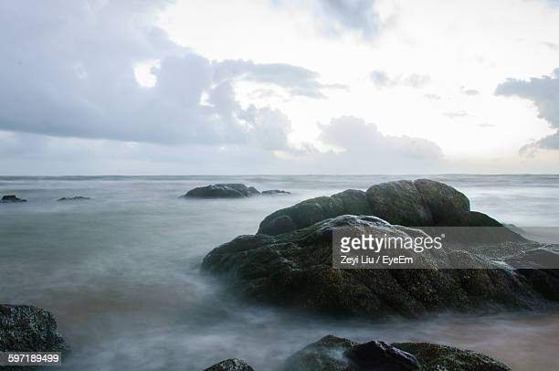 rocks emitting through sea against cloudy sky - liu he stock pictures, royalty-free photos & images