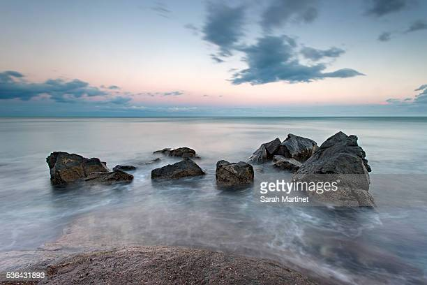 rocks immersed on sea at sunset - cap d'agde stock photos and pictures