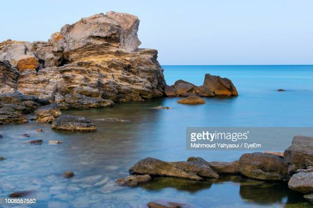 rocks in sea against clear blue sky - tunis stock pictures, royalty-free photos & images