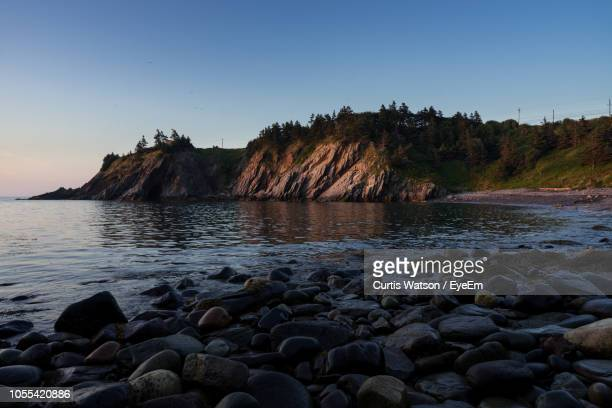 rocks in sea against clear sky - rocky coastline stock pictures, royalty-free photos & images