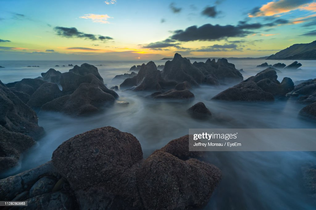 Rocks In Sea Against Sky During Sunset : Stock Photo