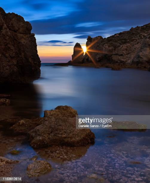 rocks in sea against sky during sunset - agrigento stock pictures, royalty-free photos & images