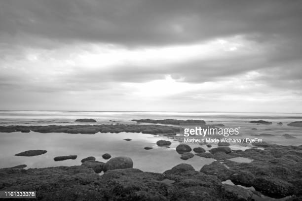 rocks in sea against sky - made widhana stock photos and pictures