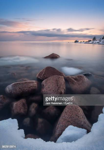 Rocks In Sea During Sunset