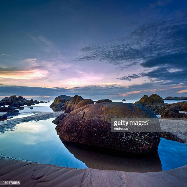 Rocks in water pool at sunrise