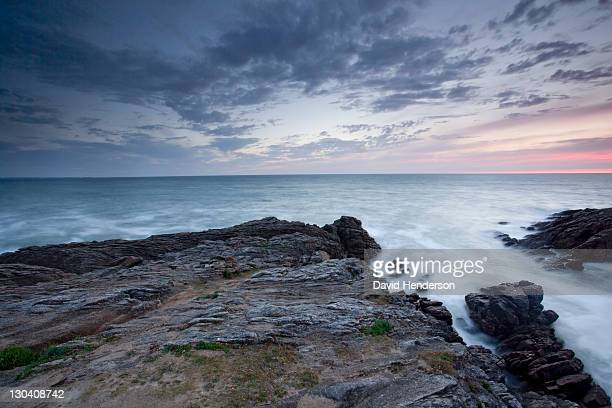 rocks jutting into ocean under sky - golfe du morbihan photos et images de collection