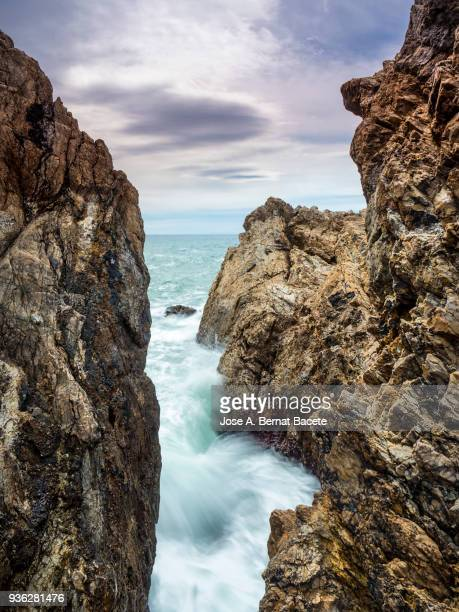Rocks of a steep cliff with the water in movement for a storm.