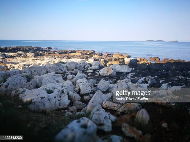 rocks on beach against clear sky - thiem stock pictures, royalty-free photos & images