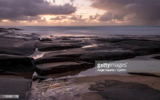 rocks on beach against sky during sunset - mooloolaba stock pictures, royalty-free photos & images