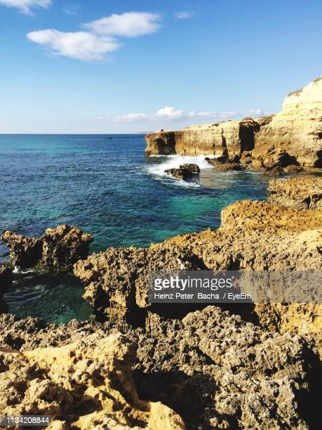 rocks on beach against sky - albufeira stock pictures, royalty-free photos & images