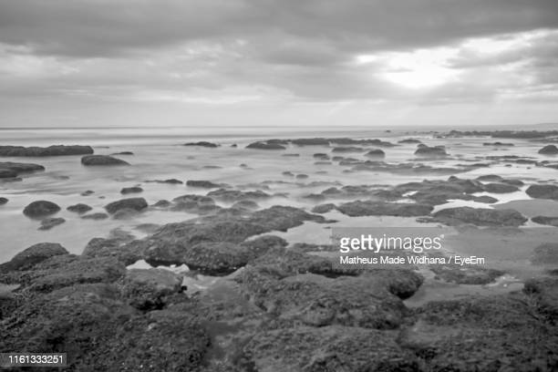 rocks on beach against sky - made widhana stock photos and pictures