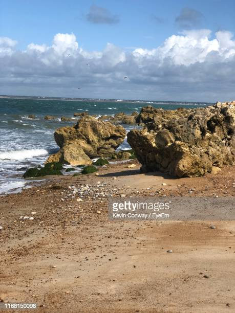 rocks on beach against sky - totland bay stock pictures, royalty-free photos & images