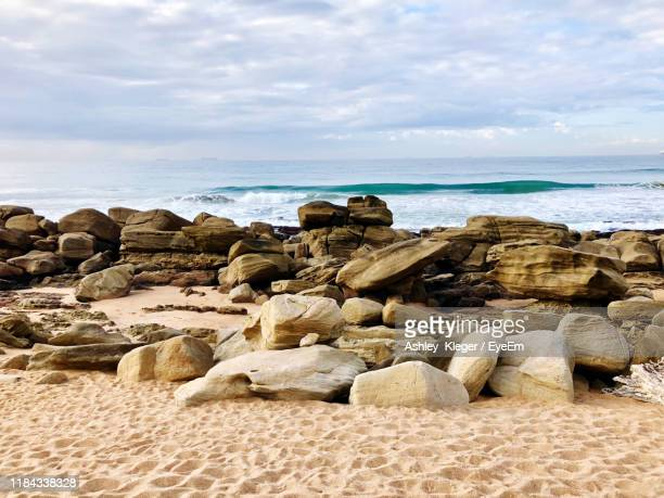 rocks on beach against sky - durban stock pictures, royalty-free photos & images