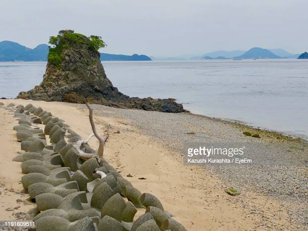 rocks on beach against sky - matsuyama ehime stock pictures, royalty-free photos & images