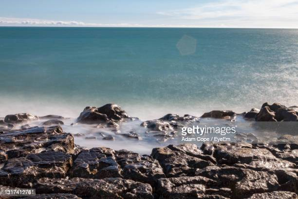 rocks on beach against sky - ilfracombe stock pictures, royalty-free photos & images