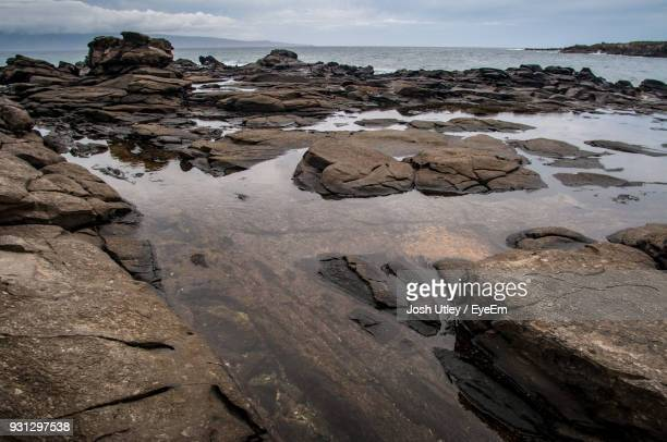 rocks on beach against sky - josh utley stock pictures, royalty-free photos & images